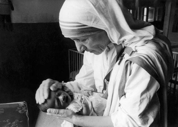 Mẹ Teresa, một nữ tu Công giáo đang cố gắng xoa dịu một đứa trẻ mồ côi mới sinh, bằng cách đặt tay lên đầu nó, trong một bệnh xá ở Calcutta vào ngày 6 tháng 9 năm 1971.