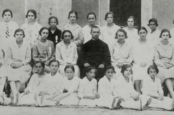 Mẹ Têrêsa ngồi phía sau là vị linh mục áo đen
